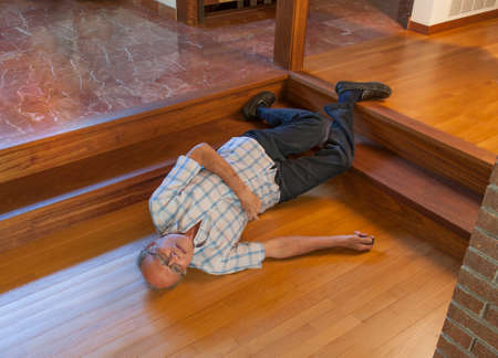 Foto de Senior man on the floor after falling down the steps and calling for help with beeper - Imagen libre de derechos