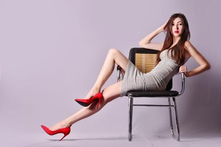Foto de girl in a striped dress posing sitting on a chair - Imagen libre de derechos