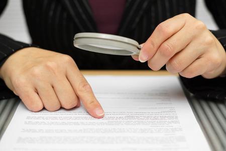 Photo pour Businesswoman looking through a magnifying glass to contract - image libre de droit