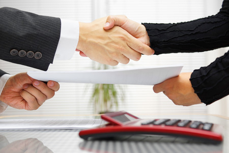 Photo pour businesswoman and businessman are handshaking and exchanging contract documents - image libre de droit