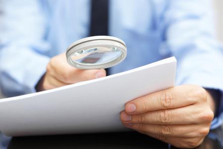 Photo pour Businessman looking through a magnifying glass to contract - image libre de droit