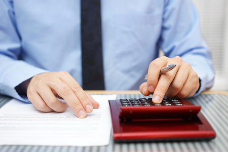 Photo for Businessman calculating  and checking articles of agreement - Royalty Free Image