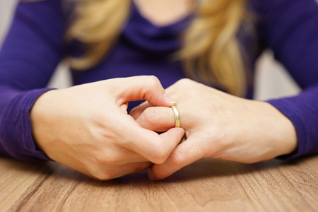 Photo pour woman is taking off the wedding ring - image libre de droit
