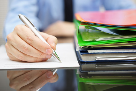 Photo for businessman is writing on document and a lot of documentation is waiting to be reviewed - Royalty Free Image
