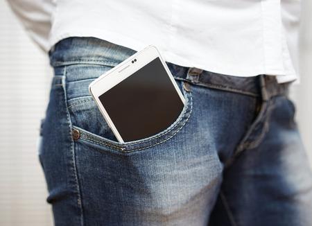 Foto de big white smart mobile phone in jeans pocket - Imagen libre de derechos
