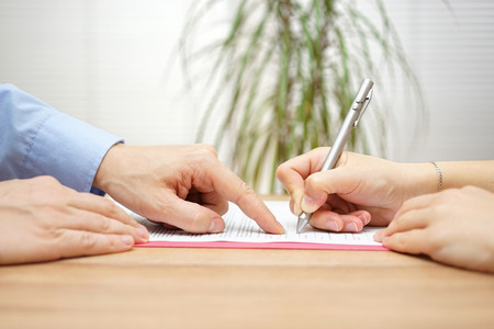 Photo for man is pointing a place where she should sign the agreement - Royalty Free Image