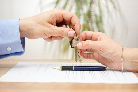 Photo pour real estate agent gives house keys to his client after signing contract - image libre de droit