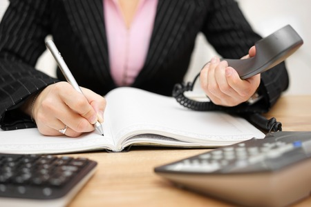 Photo for busy secretary is answering call and writing memo at the same time - Royalty Free Image