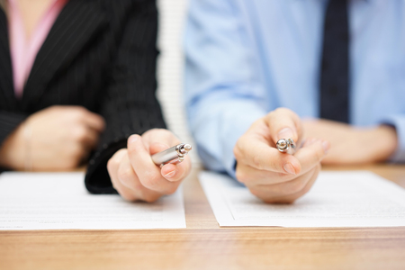 Photo for Two agents giving his client a pen to sign a deal - Royalty Free Image