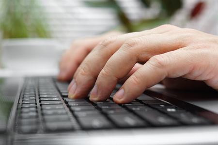 Foto de closeup of male fingers on laptop keyboard - Imagen libre de derechos
