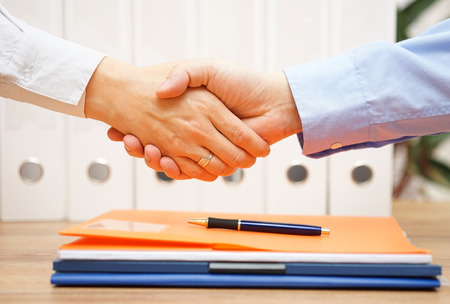 Photo for business man and woman are handshaking over documents in with office in background - Royalty Free Image