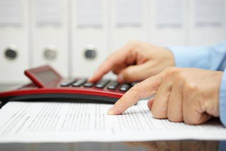 Foto de businessman is reading financial document and calculating result - Imagen libre de derechos