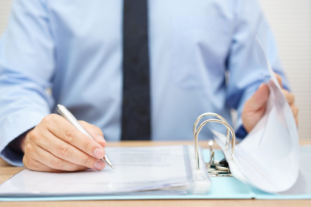 Photo pour inspector is reviewing invoices in binder - image libre de droit