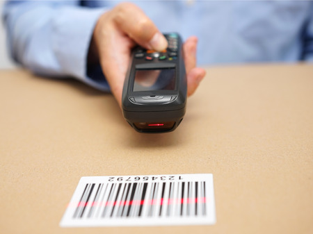 Photo pour warehouse technician inspects stocks in storage with bar code reader - image libre de droit