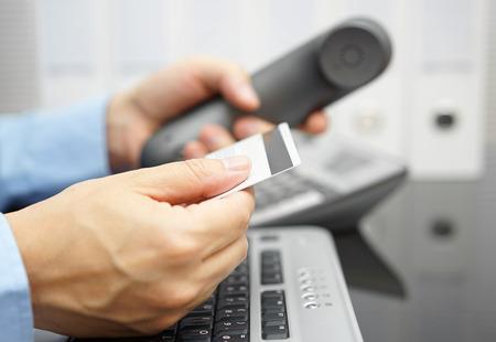 Photo pour businessman is holding credit card and calling bank for financial services - image libre de droit