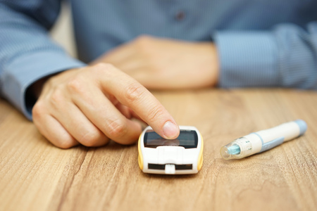 Foto per man testing glucose level with a digital glucometer, diabetes treatment - Immagine Royalty Free