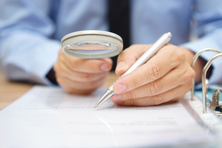 Photo for businessman is analyzing  through  magnifying glass contract and prices - Royalty Free Image