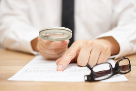 Photo pour Focused businessman is reading through  magnifying glass document - image libre de droit