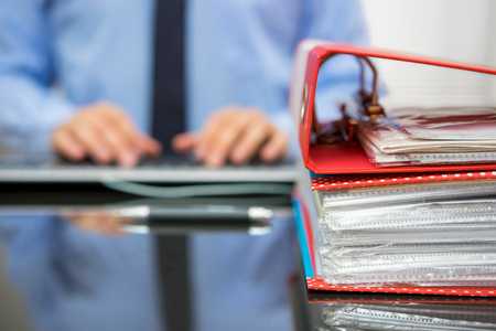 Photo pour accountant with stack of invoices is inserting data into computer database - image libre de droit