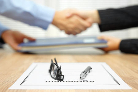 Photo pour businessman and businesswoman are shaking hands and exchanging folder  after agreement was reached - image libre de droit