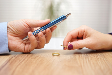 Photo for Husband is giving pen to sign divorce papers his former wife after he take off the ring form finger - Royalty Free Image