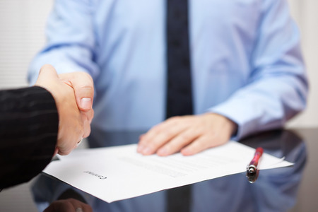 Photo for Businessman and businesswoman are handshaking over signed contract, partnership concept - Royalty Free Image
