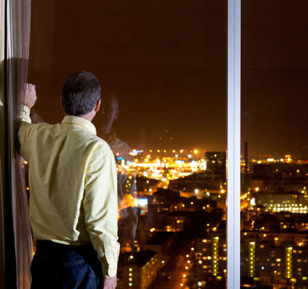 Middle aged man looking out over a city from a high window in a hotel or office