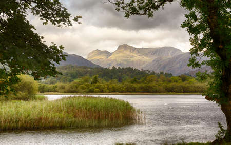 Sun rising and illuminating Langdale Pikes with Elter Water in foreground