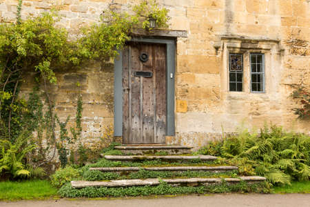 Ancient oak front door to cottage in Stanton in Cotswold or Cotswolds district of southern England in the autumn.