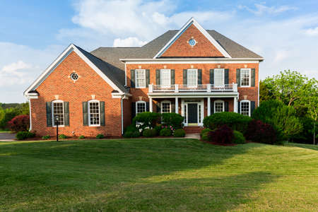 Photo pour Front of home and garage of large single family modern US house with landscaped gardens and lawn on a warm sunny summers day - image libre de droit