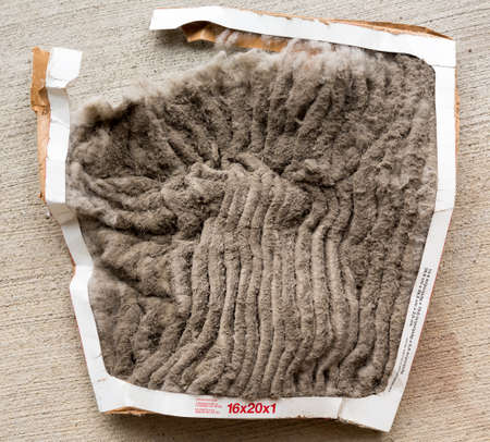 Photo for HVAC air conditioning filter clogged with dust and dirt and falling to pieces after not being changed frequently - Royalty Free Image
