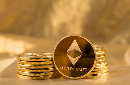 Foto de Stack of ether coins or ethereum on gold background to illustrate blockchain and cyber currency - Imagen libre de derechos