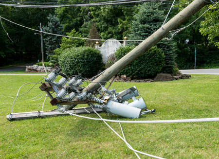 Photo for Broken snapped wooden power line post with electrical components on the ground after a storm - Royalty Free Image