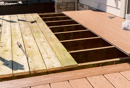 Foto de Repair and replacement of an old wooden deck or patio with modern composite plastic material - Imagen libre de derechos