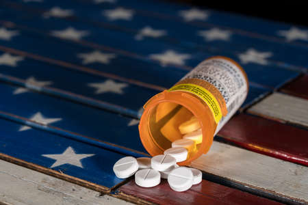 Foto de Oxycodone is the generic name for a range of opoid pain killing tablets. Prescription bottle for Oxycodone tablets and pills on wooden  USA flag - Imagen libre de derechos
