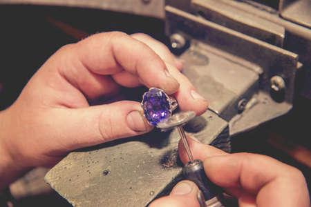 Foto de Master jeweler produces a gold ring with a big blue stone - Imagen libre de derechos