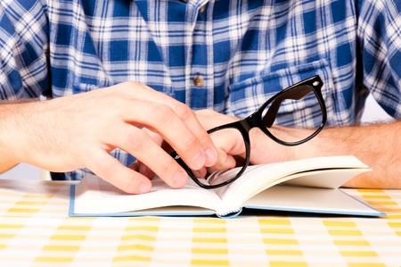 Man holding eyewear on the book