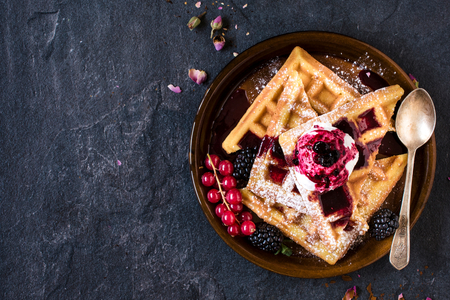 Photo for Traditional Belgian waffles with ice cream and berry fruit sauce in the plate,selective focus and blank space - Royalty Free Image