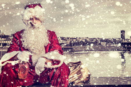 Photo for Bad Santa holding bottle of brandy and cigar in his mouth - Royalty Free Image