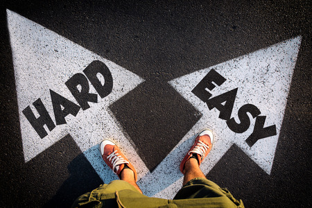 Foto de Red sheoes from above on the white arrows signs for hard and easy way,dilemmas concept - Imagen libre de derechos