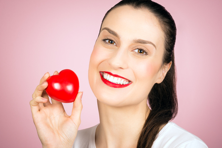 Photo pour Beautiful smiling woman is holding a little red heart in hand on pink background, love concept. - image libre de droit