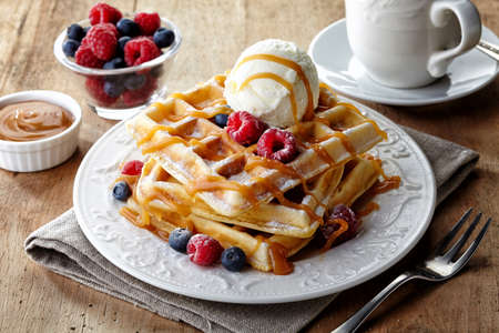 Photo for Plate of belgium waffles with ice cream, caramel sauce and fresh berries - Royalty Free Image