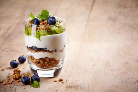 Photo for Healthy layered dessert with cream, muesli, kiwi and blueberries on wooden background with space for text - Royalty Free Image