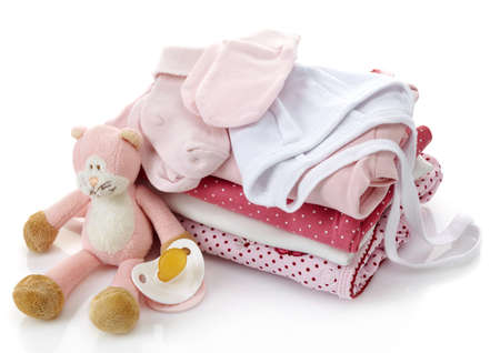 Photo pour Pile of pink baby clothes, pacifier and toy isolated on white background - image libre de droit