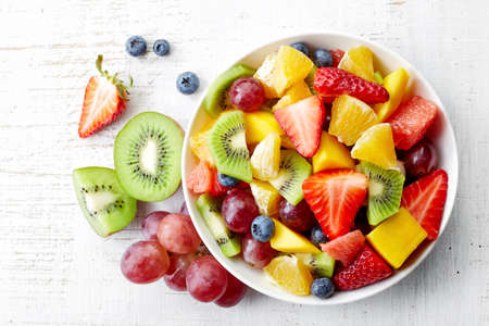 Foto de Bowl of healthy fresh fruit salad on wooden background. Top view. - Imagen libre de derechos