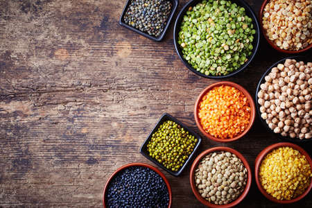 Foto de Bowls of various legumes (chickpeas, green peas, red lentils, canadian lentils, indian lentils, black lentils, green lentils; yellow peas, green mung beans) on wooden background - Imagen libre de derechos