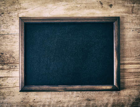 Photo for Vintage slate blank blackboard on wooden background - Royalty Free Image