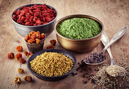 Photo pour Bowls and spoons of various superfood on wooden background - image libre de droit
