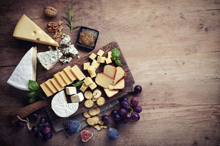 Foto de Cheese plate served with grapes, jam, figs, crackers and nuts on a wooden background - Imagen libre de derechos