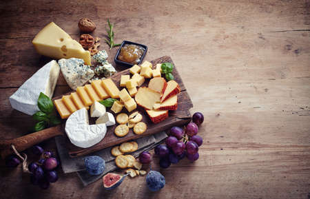 Photo for Cheese plate served with grapes, jam, figs, crackers and nuts on a wooden background - Royalty Free Image